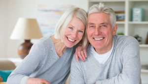 elderly couple in their living room smiling