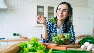 young woman eating a salad on a kitchen counter smiling
